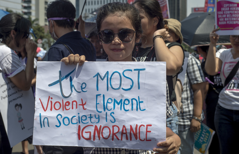A participant in Friday's march calling on the government to listen to the protesters' voices and solve problems affecting women in Indonesia. (JG Photo/Yudha Baskoro)