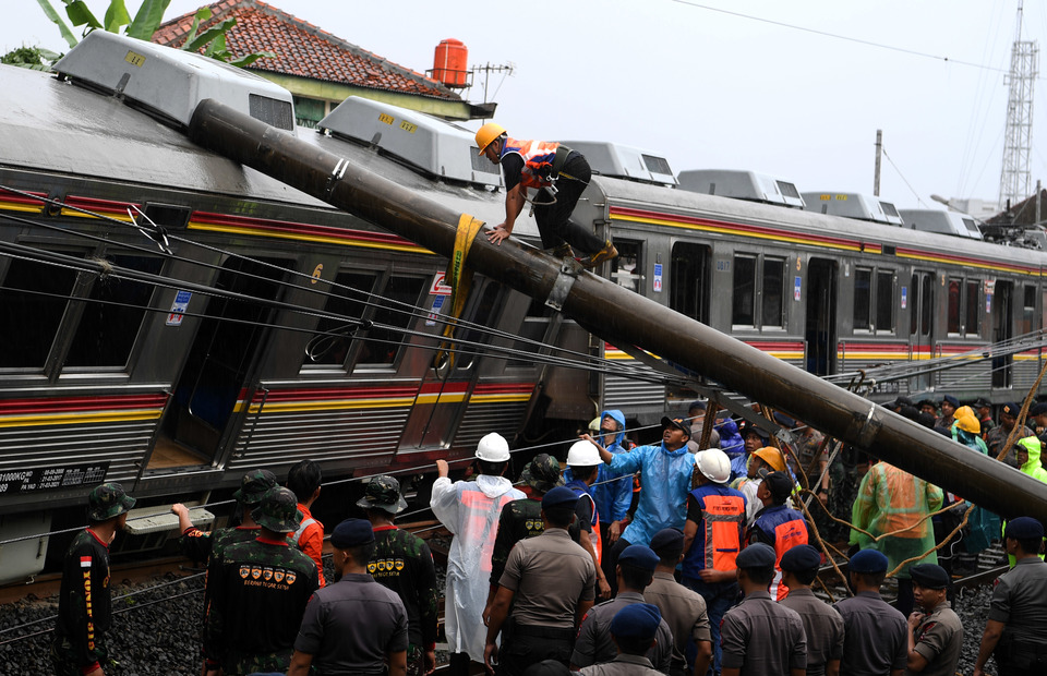 Officers tried to move the electric pole that hit the Commuter Line 1722 KRL which derailed at the Kebon Pedes, Tanah Sareal, Bogor regency, West Java on Sunday (10/03)
