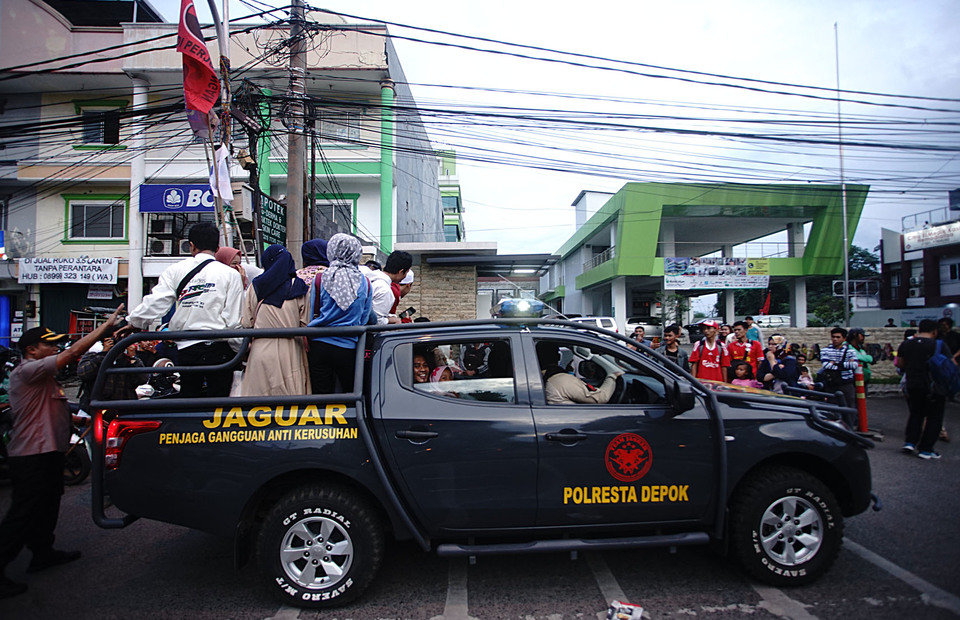 The Depok City police vehicle transports passengers who stranded on Jalan Kartini Pancoran Mas in Depok, West Java, Sunday (10/03).