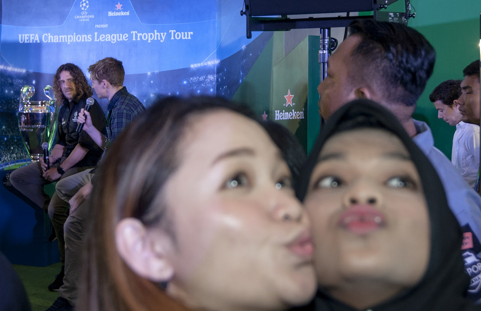 Two journalists take a selfie with Carles Puyol as a background during the UCL trophy tour press conference in Lotte Shopping Avenue, South Jakarta on Monday (11/03) (JG Photo/Yudha Baskoro)