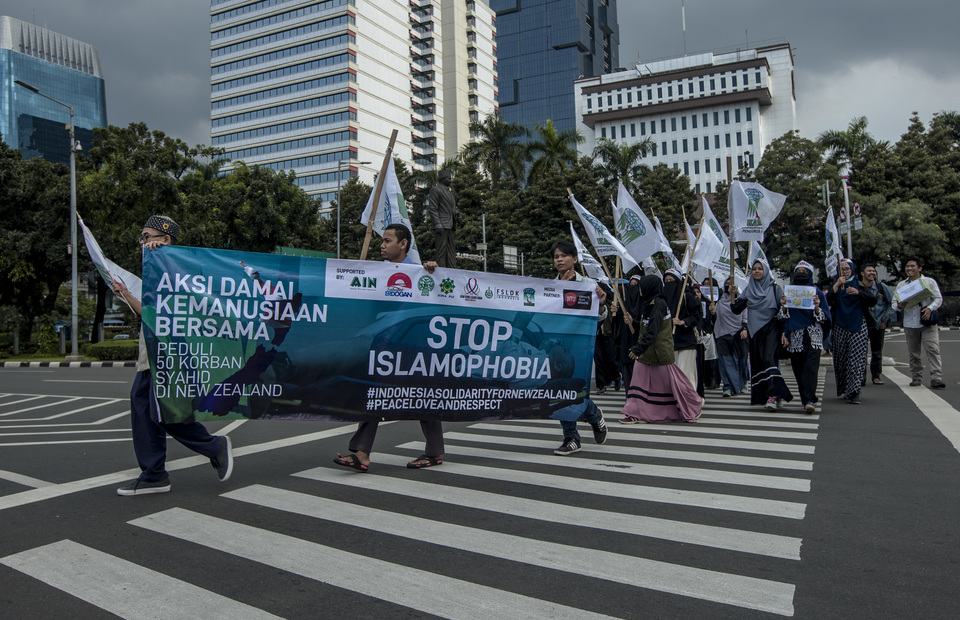 Indonesian muslims carry a banner said 'Stop Islamophobia' during support action in front of Horse Statue, Central Jakarta on Friday (22/03) They support New Zealand