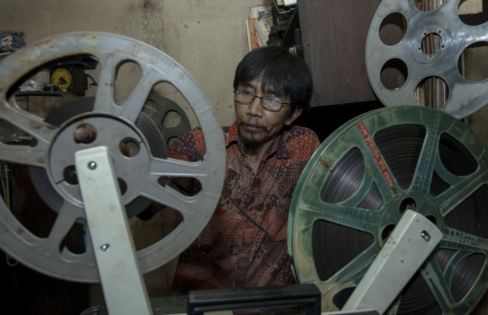 Danny cleans his old projector in his small studio in Senen, Central Jakarta on Tuesday (26/03) He always conducts a routine check because there is no spare part left to repair the projector. (JG Photo/Yudha Baskoro)