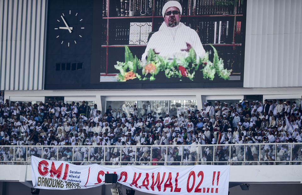 Firebrand cleric Rizieq Shihab, leader of the hardline Islamic Defenders Front (FPI), appears in the video to deliver a message to the crowd during the rally.
