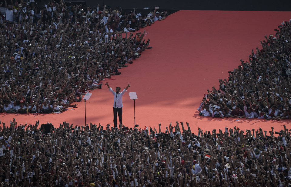 Joko Widodo raises his hands and greets his supporters during his final campaign in GBK stadium on Saturday (13/04) The crowd gather at the stadium since 10 a.m. and waiting for the incumbent candidate to give oration in the afternoon. (ANTARA FOTO/Nova Wahyudi)