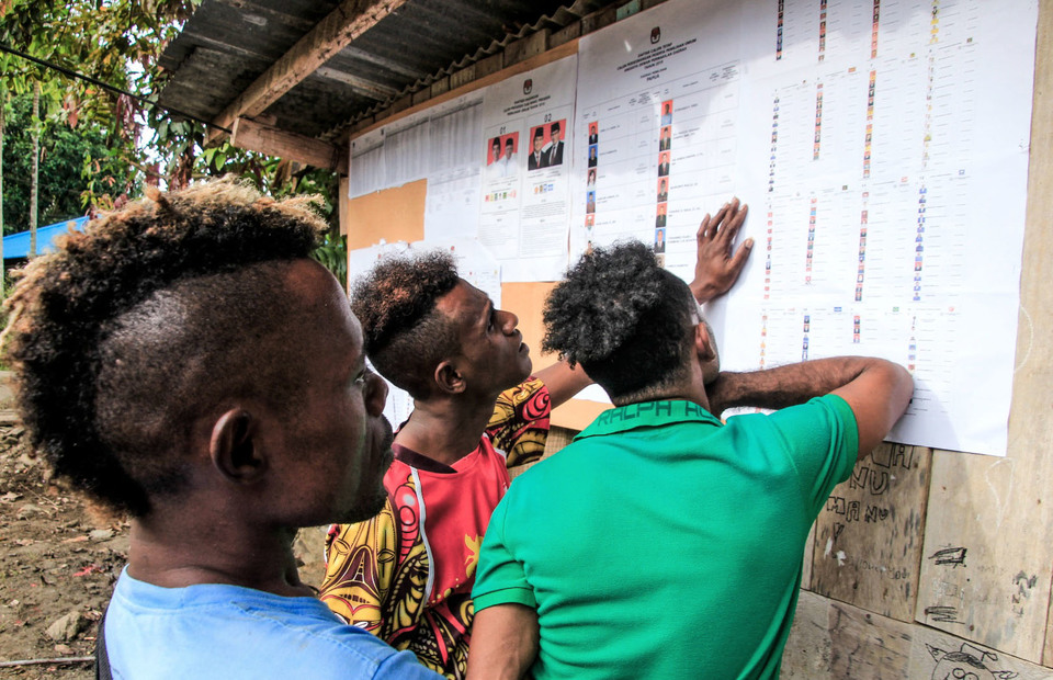 Residents scan the list of legislative candidates in the 2019 elections at a polling station in Wahno village in Jayapura district, Papua. (Antara Photo/Gusti Tanati)