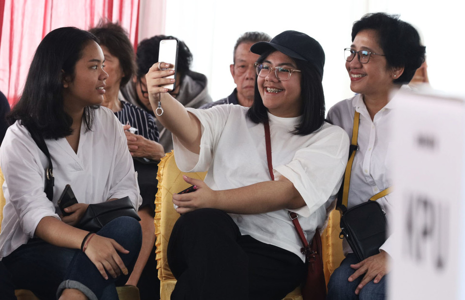 Residents take a selfie at a polling station at the offices of the State Administration Agency in Central Jakarta. (JG Photo/Yudha Baskoro)