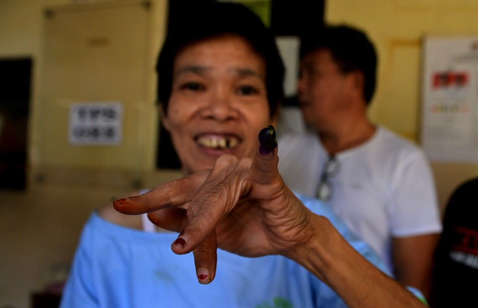 A person with mental disability showing off an inked finger after voting at Ratumbuysang Hospital in Manado, North Sulawesi. About 140 people have registered to vote at the hospital. (Antara Photo/Adwit B Pramono)