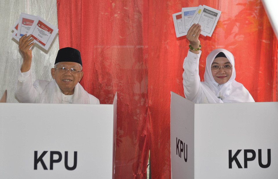 Mar'ruf Amin and his wife Wuri Estu Handayani hold up ballot papers before voting in Koja, North Jakarta. (Antara Photo/Aprillio Akbar)
