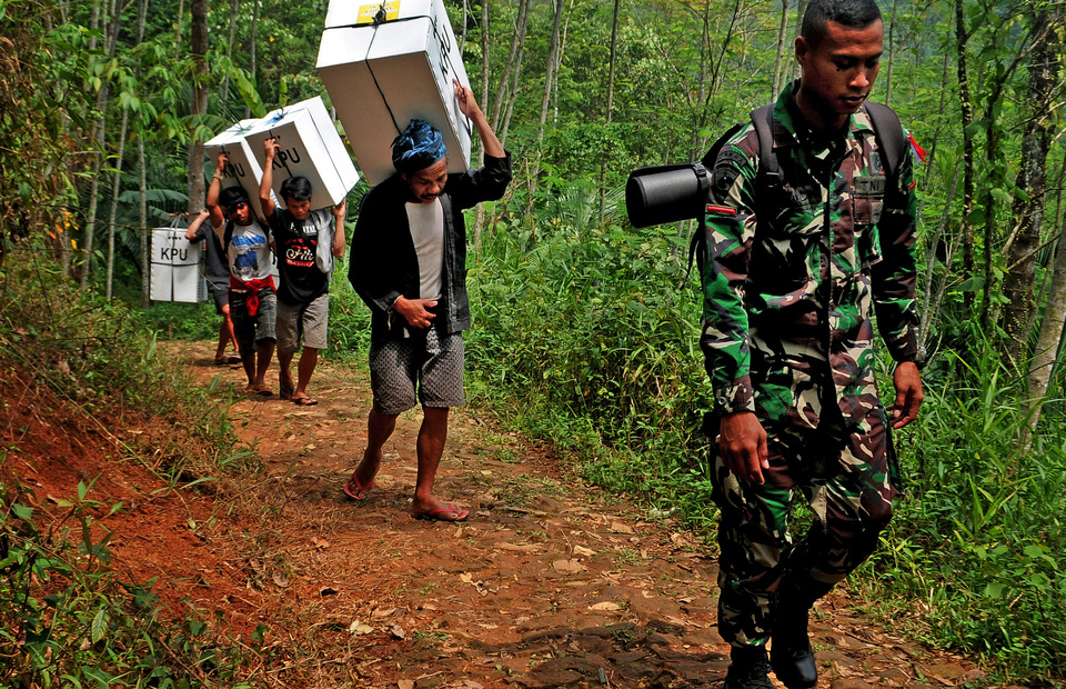 In some cases, election workers may travel up to three hours  on foot to reach polling stations, such as these pictured above, carrying ballot papers to a Baduy village in Banten. (Antara Photo/Muhammad Bagus Khoirunas)