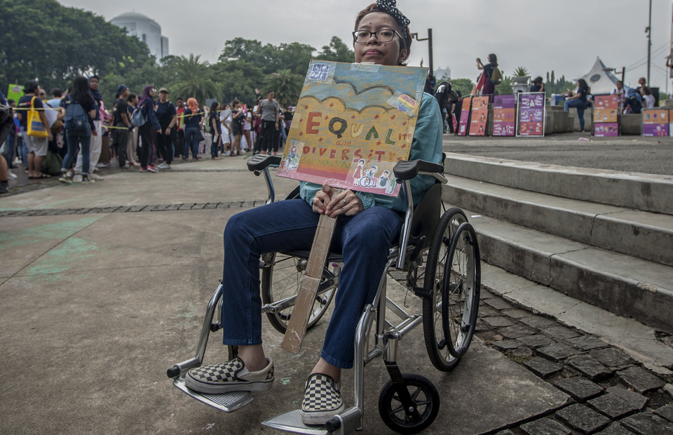 People with disability shows her placard reads equality and diversity during the Women