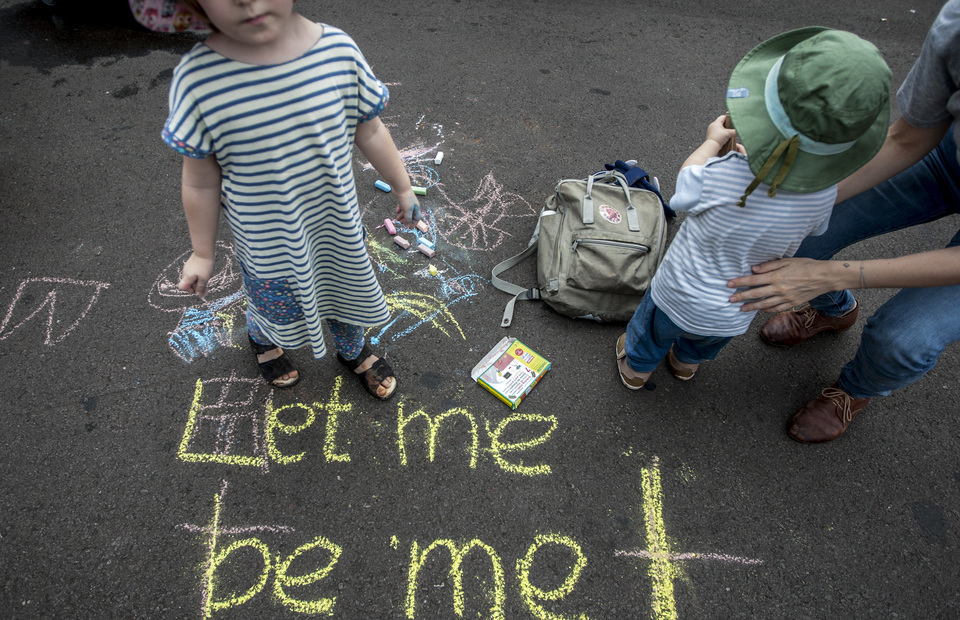 Children play and draw with chalk during women
