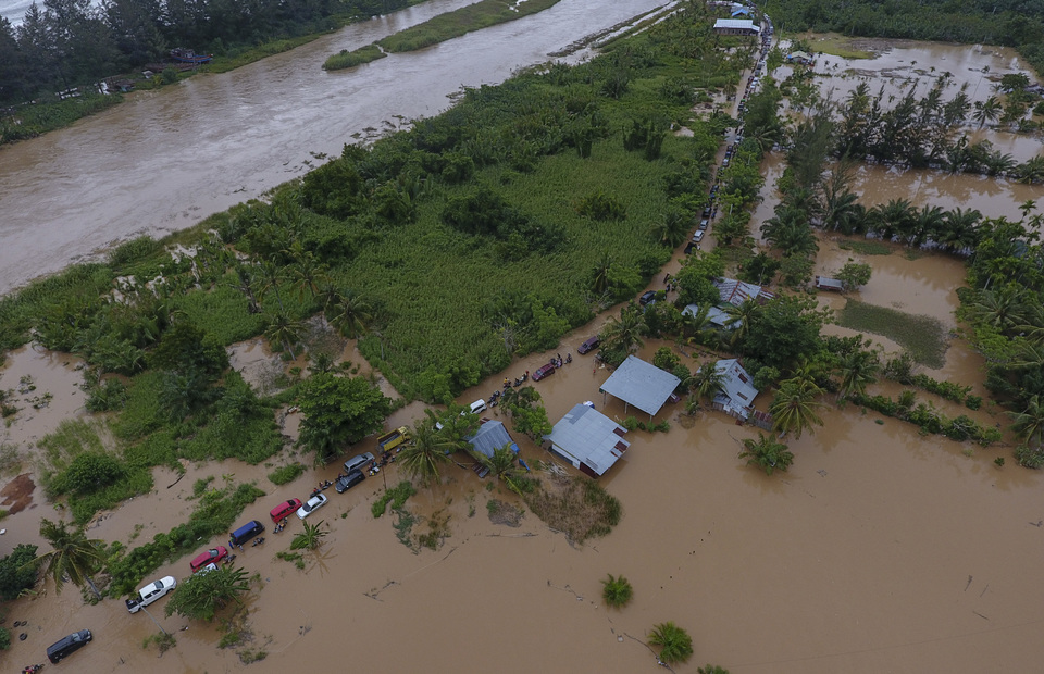 An aerial photo shows vehicles crossing a flooded area in the Bengkulu on Saturday. (Antara Photo/David Muharmansyah)