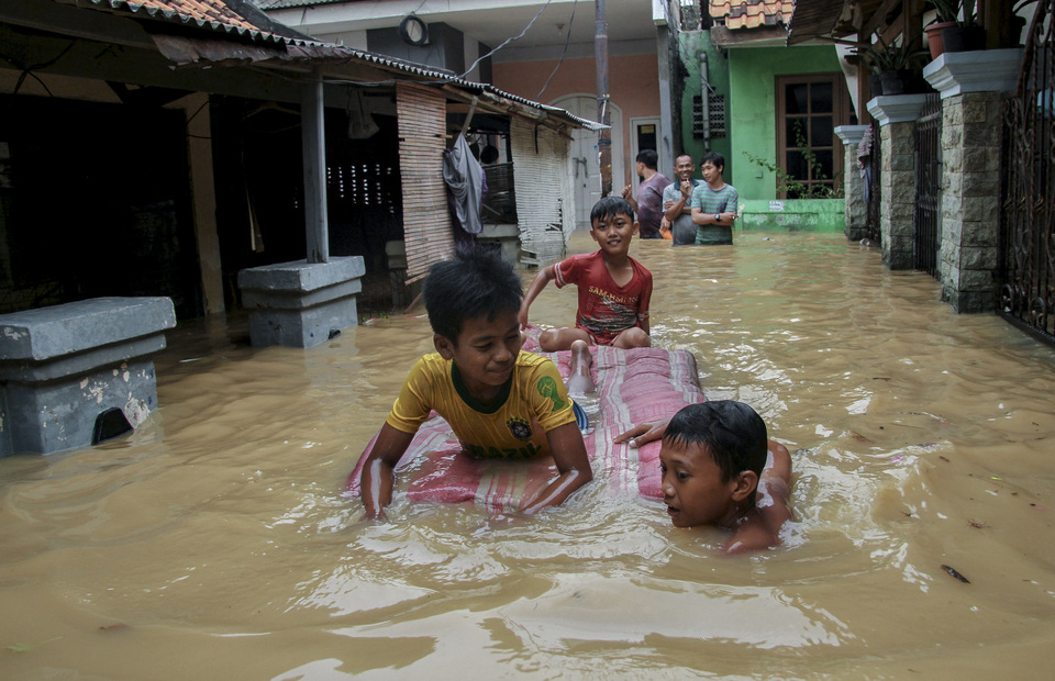 Children play in a flooded backstreet in Cililitan Kecil, East Jakarta, on Friday. Several homes were inundated after the Ciliwung River overflowed. (Antara Photo/Risky Andrianto)