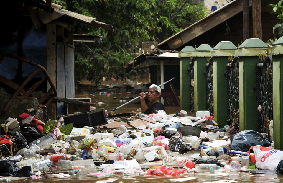 A resident tries to clear garbage that was washed up by floodwaters in Cililitan Kecil. (Antara Photo/Risky Andrianto)