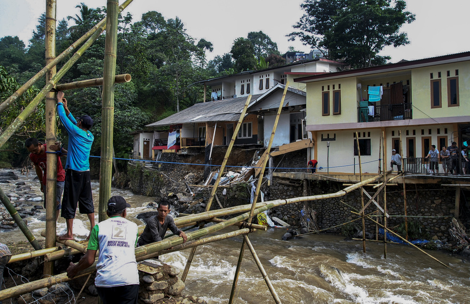 Residents work together to build a temporary bridge over the Ciliwung River in Muara village in Bogor district, West Java, on Sunday after the main bridge collapsed due to flooding on Thursday night. (Antara Photo/Arif Firmansyah)