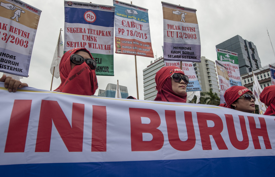 Women workers hold posters as they protest during a May Day rally near the Arjuna Wiwaha Statue in Central Jakarta on Wednesday (01/05) (JG Photo/Yudha Baskoro)