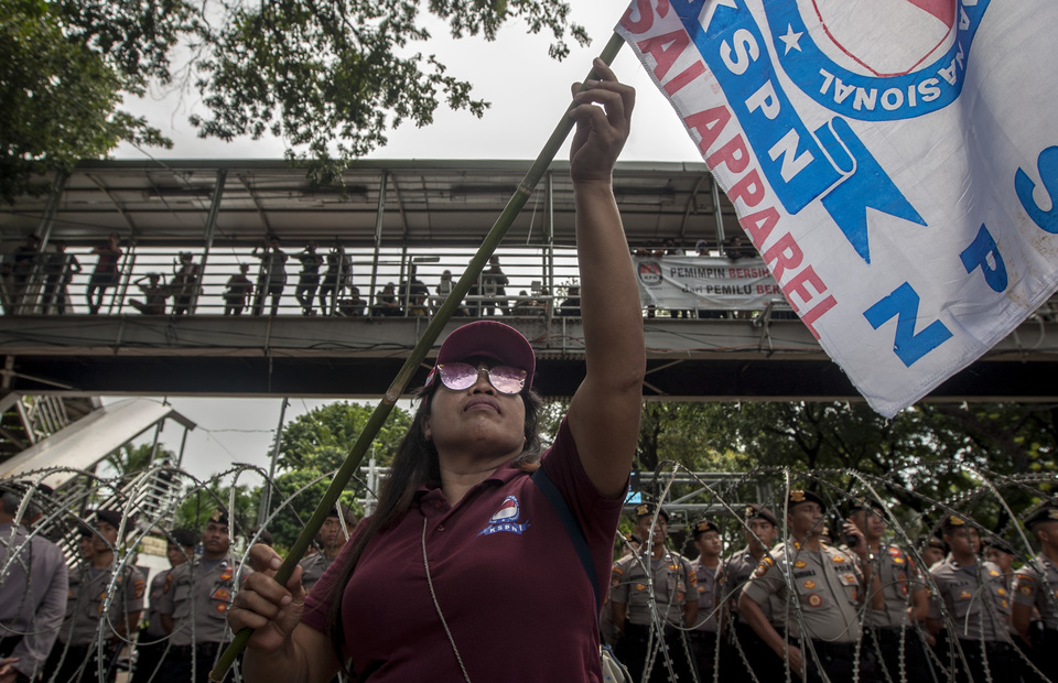 A woman worker waves a flag in front of police barricade and iron fence during May Day protest in front of Sapta Pesona Building, Central Jakarta on Wednesday (01/05) (JG Photo/Yudha Baskoro)
