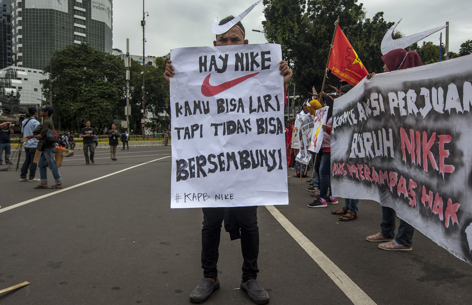 Nike Factory workers hold a poster reads Hay Nike, you can run but you can not hide during a May Day protest in front of Arjuna Wiwaha Statue, Central Jakarta on Wednesday (01/05) (JG Photo/Yudha Baskoro)