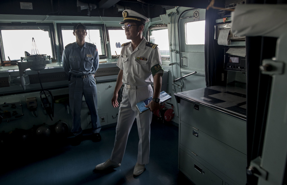 Two JS Samidare personnels stand inside the cockpit during the open ship for Indonesian journalists in Tanjung Priok Port, North Jakarta on Wednesday (08/05) (JG Photo/Yudha Baskoro)