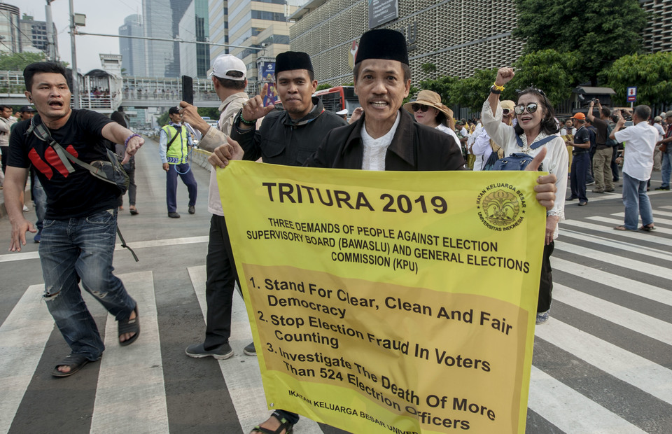 A protester carry a placard reads Tritura 2019, Three Peoples Demands during the protest in front of Bawaslu, Central Jakarta on Thursday (09/05) (JG Photo/Yudha Baskoro)