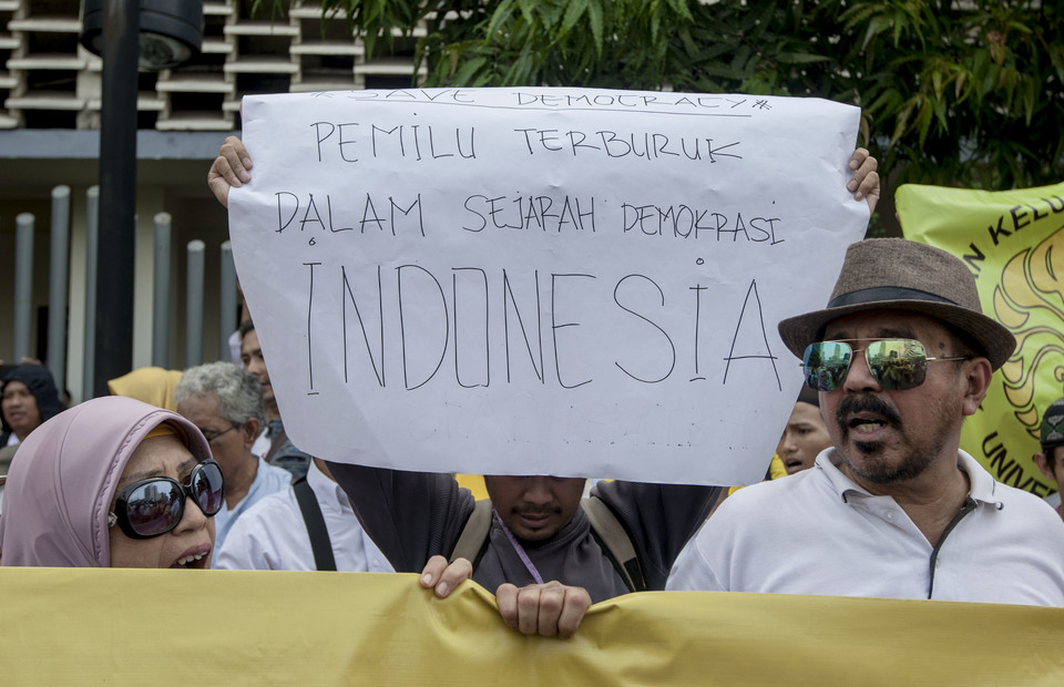 A protester shows a placard reads the worst election in Indonesia history during the protest in front of Bawaslu, Central Jakarta on Thursday (09/05) (JG Photo/Yudha Baskoro)