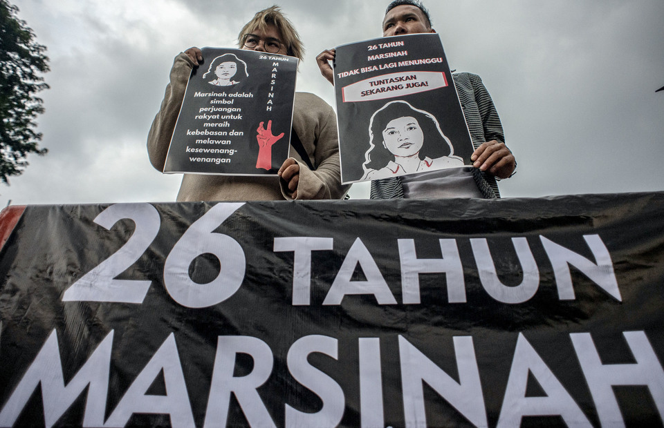 Two protesters carry placard demanded that the government seriously and thoroughly investigate the case of Marsinah. (Antara Photo/Aprillio Akbar)