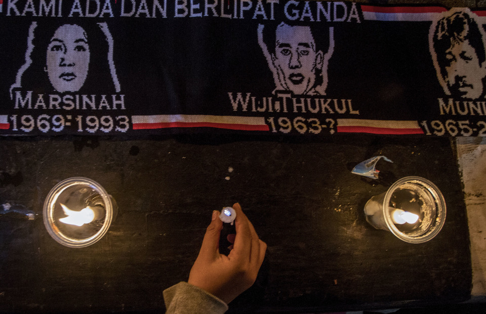 Bandung residents lit candles on a scarf pictures three Indonesian human rights heroine; Marsinah, Wiji Thukul and Munir during the 585th kamisan in Vanda Park, Bandung, West Java on Thursday (09/05) (Antara Photo / Novrian Arbi)