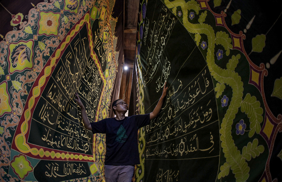 A man unfurled a batik with Al-Quran batik motifs as he visits Batik tourism site at Mahkota Batik Laweyan, Solo, Central Java on Thursday (09/05). The batik written in the verses of the Koran was made by the owner of a local batik business to invite the public to learn to write, read and understand the Koran, while attracting tourist visits in the Batik Laweyan Village. (Antara Photo / Maulana Surya )