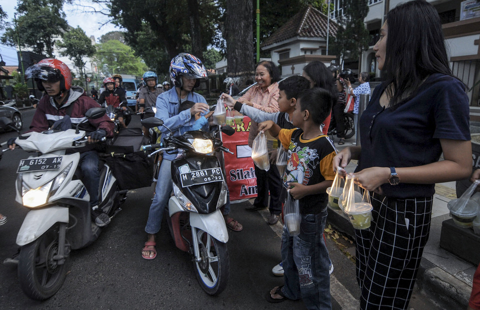 Indonesian Catholics (right) distributed food during iftar to motorists in front of the Santo Paulus Miki Catholic Church, Salatiga, Central Java on Thursday (09/05). A total of 300 takjil packages is distributed to residents during iftar to increasing religious tolerance awareness in Salatiga.(Antara Photo/ Aloysius Jarot Nugroho)