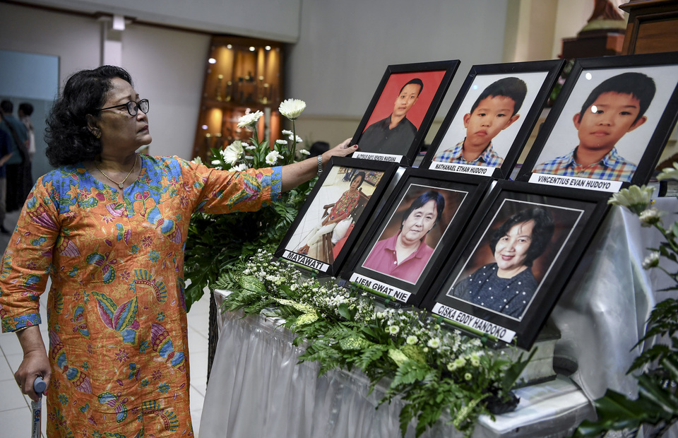 A woman mourns in front of past photos of Surabaya bombings victims in The Immaculate Saint Mary Catholic Church, Surabaya, East Java on Monday (13/05) (Antara Photo/Zabur Karuru)