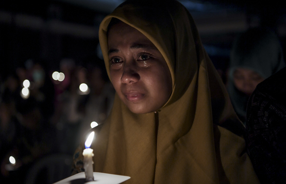 A muslim woman cries as she attends the memorial service to remembering the victims of Surabaya bombings in Immaculate Saint Mary Catholic Church, Surabaya, East Java on Monday (13/05) (Antara Photo/Zabur Karuru)