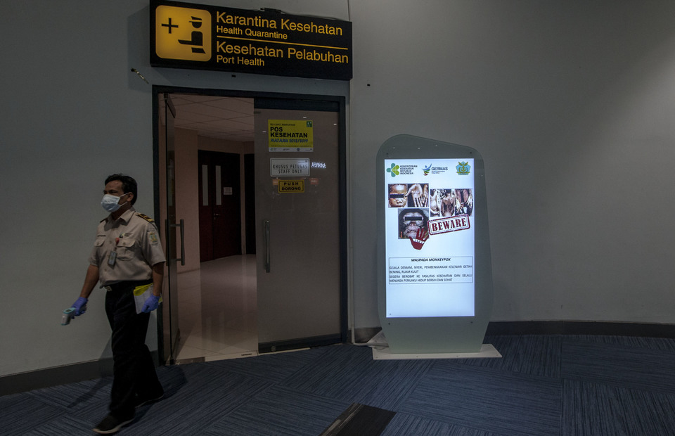 Port Health Authority officer walks near the monkeypox virus announcement in digital board in front of health quarantine room as he conducts a routine check during monkeypox preventive act in Soekarno Hatta International Airport, Tangerang, Banten on Wednesday (15/05) (JG Photo/Yudha Baskoro)