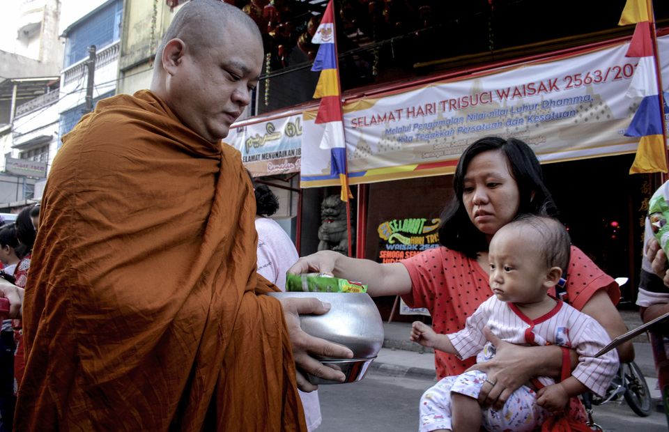Monks receive charity or alms from residents during the Pindapata procession in Makassar, South Sulawesi on Sunday (19/05). (Antara Photo / Arnas Padda)