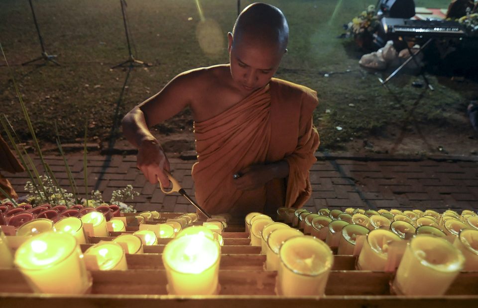 A monk lights candles for the rendering of services during Vesak at Sewu Temple, Prambanan, Klaten, Central Java on Saturday (18/05). The ritual means pray for the deceased ancestors and humanity on earth (Antara Photo/ Aloysius Jarot Nugroho)