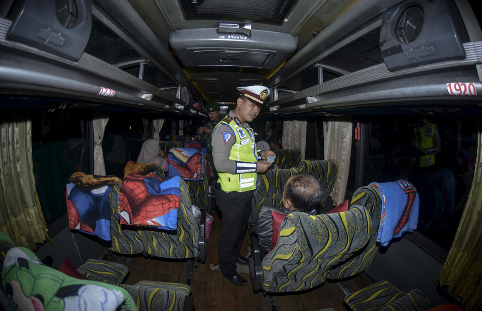 Police personnel conduct identity check on bus passengers in Pantura Situbondo highway, East Java, on Saturday (18/05) Police in Situbondo increase their security to prevent mass mobization protest to Jakarta. (Antara Photo/ Seno)