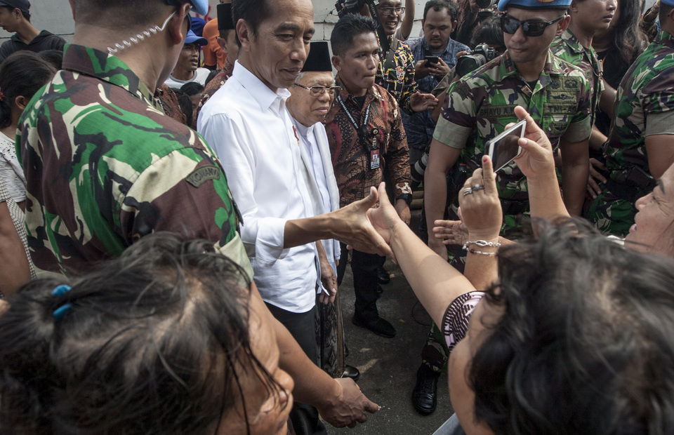 President Joko Widodo shakes hand with Kampung Deret resident as he visits the kampung to gives speeches to declare his victory in 2019 Presidential Elections on Tuesday (21/05) (JG Photo/Yudha Baskoro)