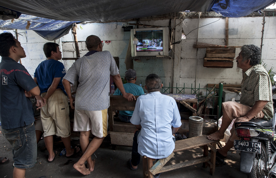 Kampung Deret residents watch news about 2019 election on TV together in Jalan Tanah Tinggi I, Central Jakarta on Tuesday (21/05) (JG Photo/Yudha Baskoro)