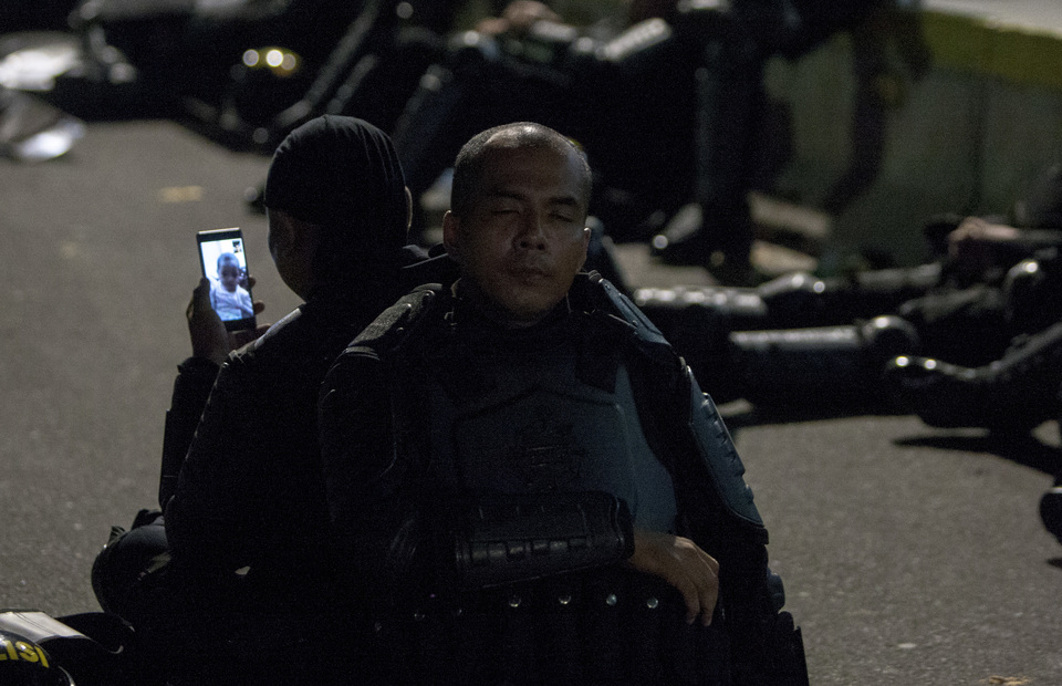 Police officer is on video call with his child as the protesters break to perform tarawih prayers during the may 21 rally in front of Elections Supervisory Agency (Bawaslu) headquarters in Jalan Thamrin, Central Jakarta on Tuesday (21/05) (JG Photo/Yudha Baskoro)