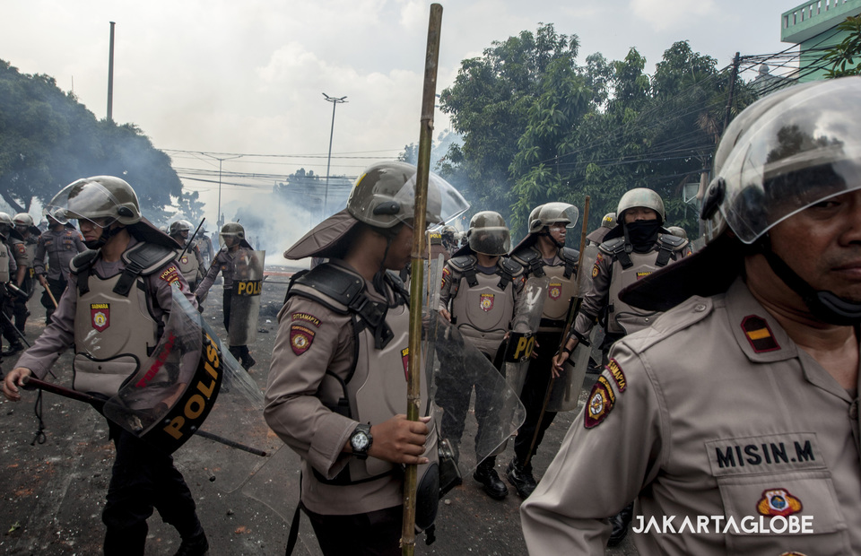 Police go back after throw a tear gas to the crowd during a may 22 riots in KS Tubun, Central Jakarta on Wednesday (22/05) (JG Photo/Yudha Baskoro)