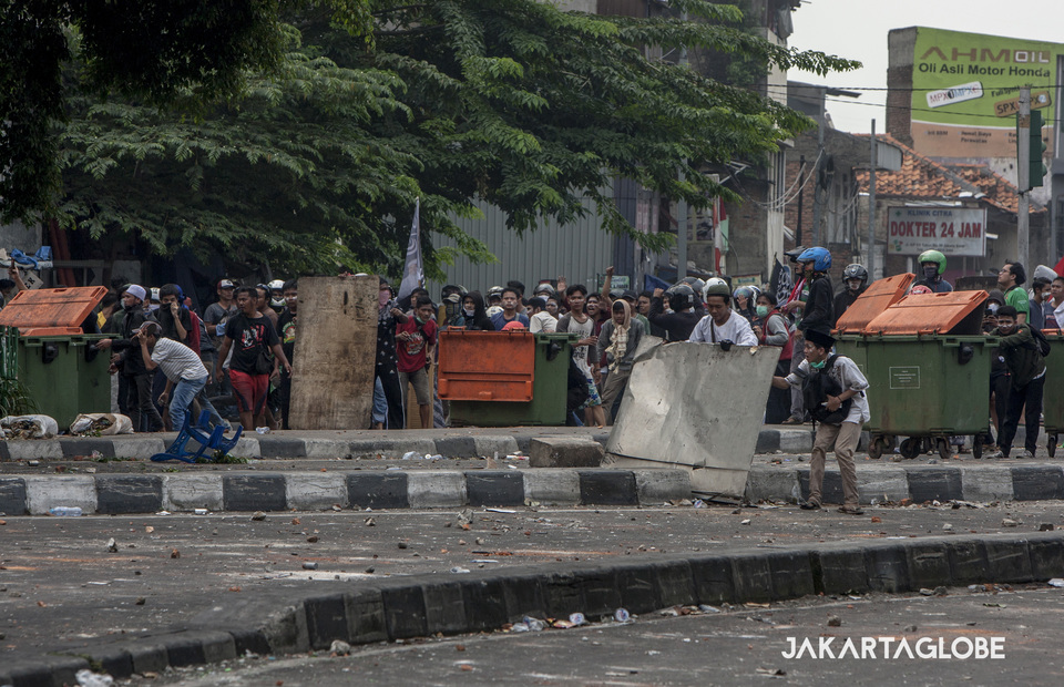Crowds stand behind trash bin to take defense againts police during the riots in KS Tubun, Central Jakarta on Wednesday (22/05) (JG Photo/Yudha Baskoro)