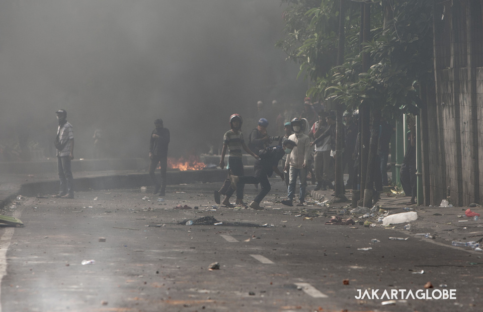 Protesters throw stones and fireworks to police officers during the riots in KS Tubun street, Central Jakarta on Wednesday (22/05) (JG Photo/Yudha Baskoro)