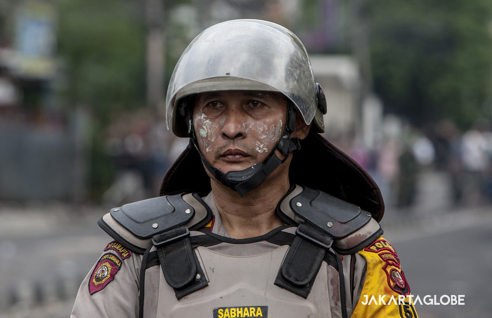 A police officer use toothpaste to decrease the effect of tear gas during riots in KS Tubun street, Central Jakarta on Wednesday (22/05) (JG Photo/Yudha Baskoro)