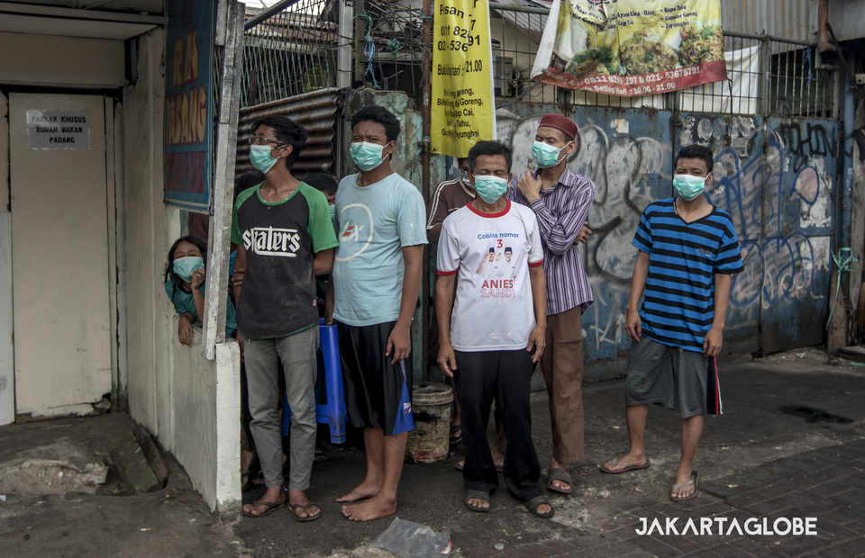 Resident in KS Tubun street are being evacuated from their home and wearing mask to avoid tear gas during riots on Wednesday (22/05) (JG Photo/Yudha Baskoro)