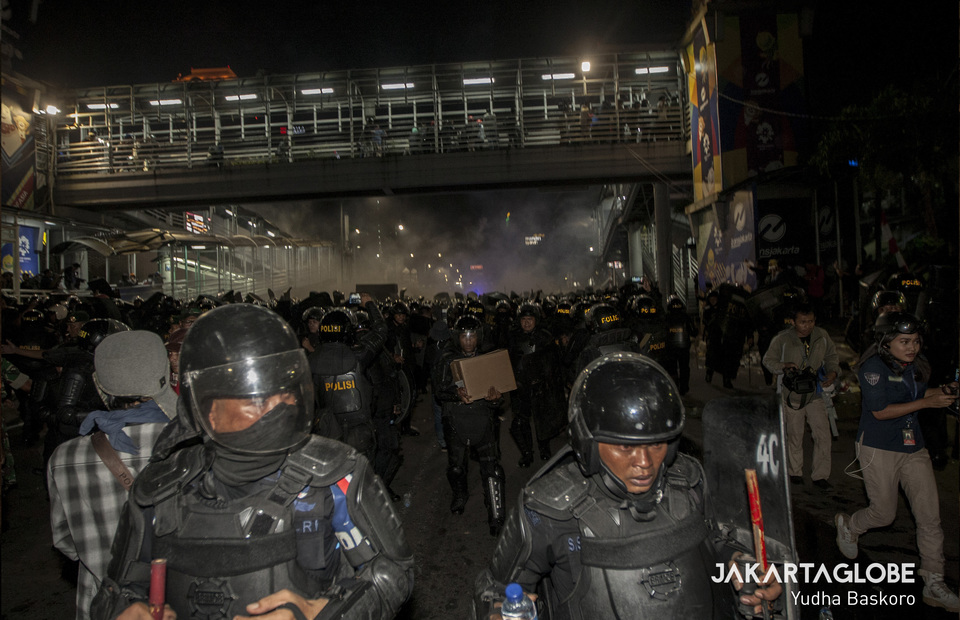 Police personnels run to avoid firecrackers and molotov cocktail during May 22 riot in front of Election Supervisory Agency, or Bawaslu headquarters in Central Jakarta on Wednesday (22/05) (JG Photo/Yudha Baskoro)