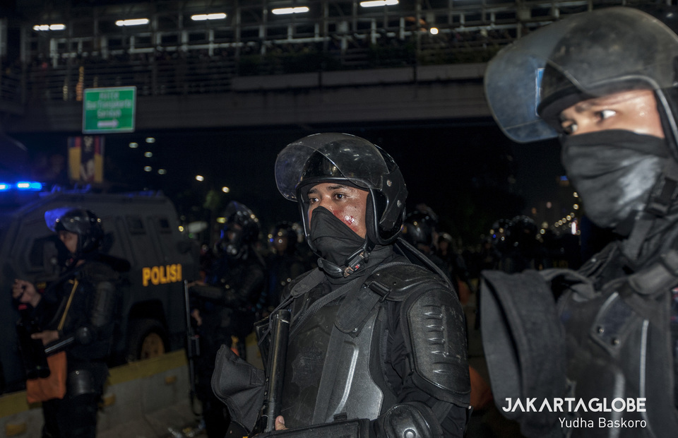 Police personnel bleeding on his face after a firecrackers and molotov cocktail explode in front of him during May 22 riot in Thamrin, Central Jakarta on Wednesday (22/05) (JG Photo/Yudha Baskoro)