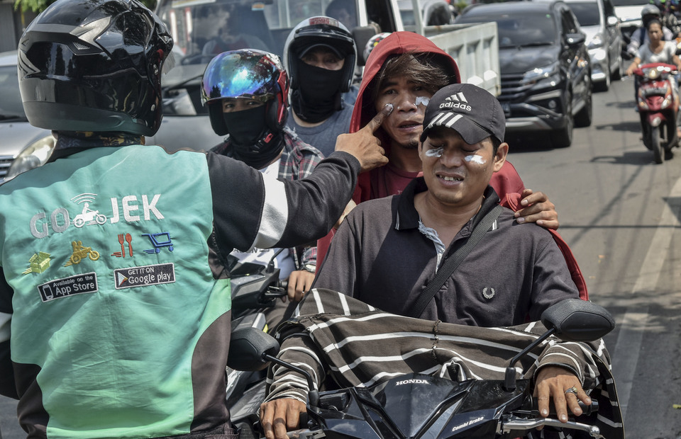 A resident applied toothpaste to other residents affected by the remaining tear gas residue on Jalan Kemanggisan Raya, Slipi, West Jakarta on Thursday (23/05)( Antara Photo/Aditya Pradana Putra)