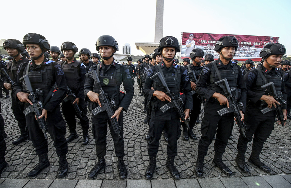 Indonesian National Police officers stand on guard in front of National Monument, Central Jakarta on Tuesday (28/05) 93,589 National Police personnels will be deployed around the archipelago to secure mudik lebaran (Antara Photo/Rivan Awal Lingga)