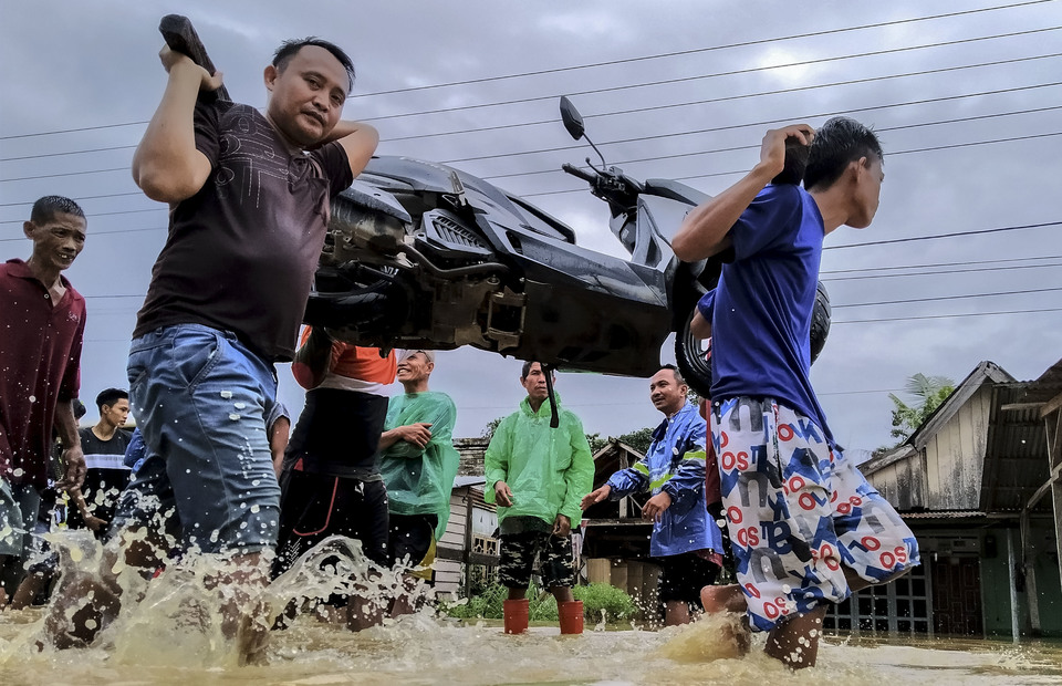 Residents rescue their motorbikes and belongings during flash flood near Konaweha River in Ameroro Village, Konawe, Southeast Sulawesi on Sunday (09/06). (Antara Photo/Jojon)