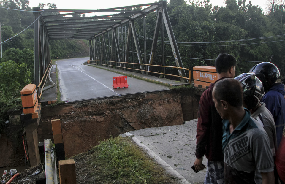 Residents gather in front of the broken Ameroro bridge, the trans-Sulawesi access road damaged by flash flood on Monday (10/06). (Antara Photo/Jojon)