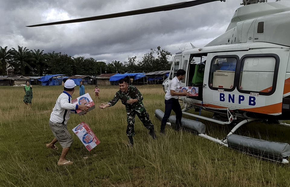 Flash flood victims receive logistics assistance contains of instant food which is transported using BPBD helicopters at Wiwirano Sub-District, North Konawe, Southeast Sulawesi on Monday (10/06). (Antara Photo/HumasKodim1417)